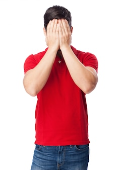 Guy covering his face with hands on white background