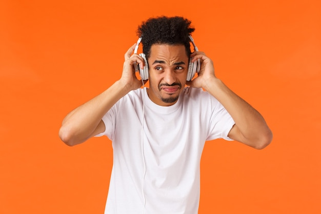 Guy cringing and grimacing from dislike and disapproval, unwilling hear friends fighting, put-on headphones listen music instead of quarrel, standing uncomfortable over orange background