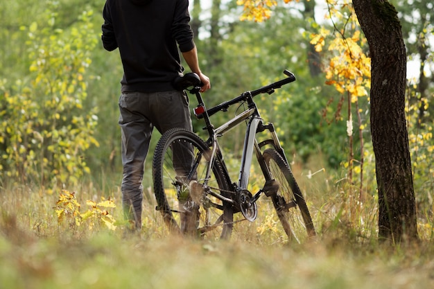 Guy cyclist in autumn forest in october. active lifestyle. outdoor activities and cycling