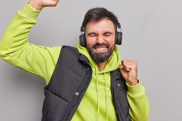 좋아하는 음악에 맞춰 춤을 추는 남자는 팔을 들고 미소를 지으며 즐겁게 무선 헤드폰을 사용하여 노래의 모든 부분을 캐치하고 회색으로 격리된 캐주얼 후드티와 조끼를 입습니다