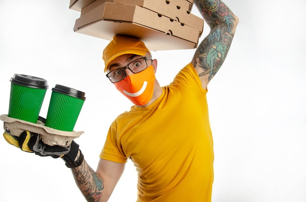 The guy delivering packages in a virus-proof mask, the courier with pizza and coffee. security during quarantine