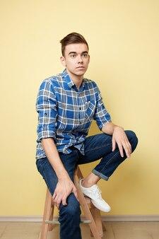 格子縞のシャツとジーンズに身を包んだ男は、スタジオの黄色の背景のスツールに座っています。