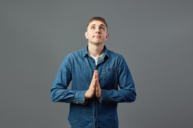 白いtシャツ、ジーンズ、ジーンズのシャツを着た男が、灰色の背景で空を見上げて祈るように手を組んで立っています。