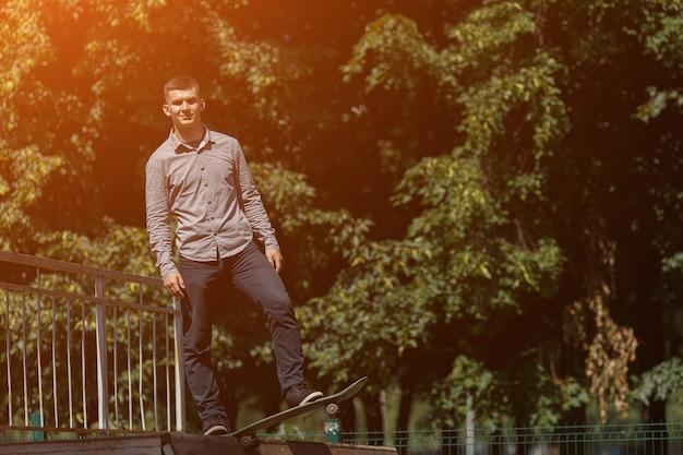 晴れた夏の日、コピースペースのスケートパークのスケートボードに立っているスタイリッシュなシャツのスニーカーとズボンを着た男。日光