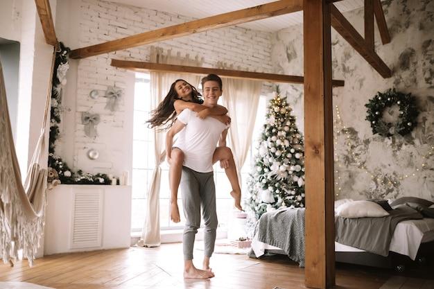흰색 티셔츠와 반바지를 입은 남자는 나무 기둥, 새해 나무, 선물, 양초로 장식된 아늑한 방에서 소녀를 등에 업고 있습니다.