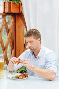 Парень ест куриные крылышки на гриле и пьет пиво в ресторане
