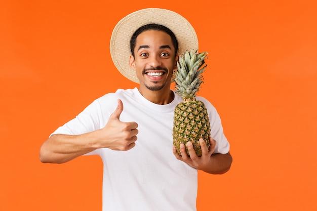 Парень наслаждается поездкой, рекомендую туристическое агентство. радостный улыбающийся афроамериканец красивый молодой человек показывает палец вверх, держа ананас и улыбаясь, отдыхая в отпуске, оранжевый