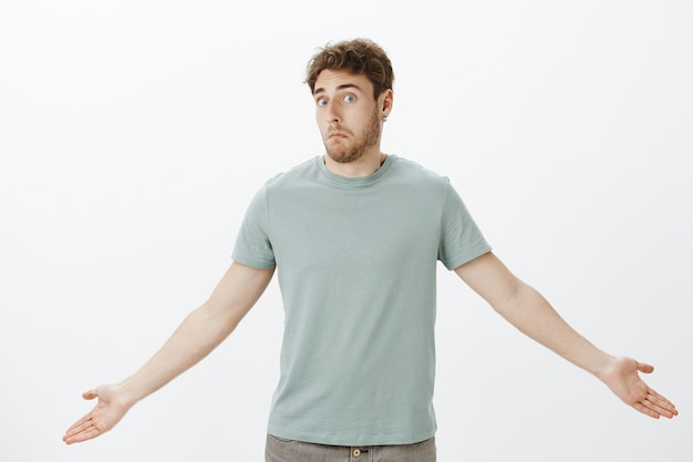 Guy feeling confused after loosing wallet. portrait of questioned timid attractive man in t-shirt, spreading palms and shrugging with awkward unaware expression
