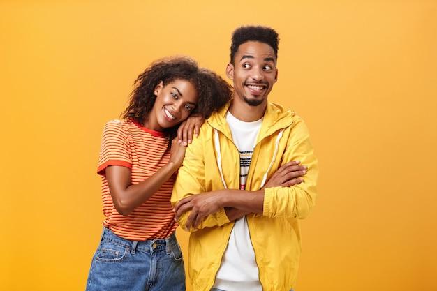 Парень, чувствуя себя счастливой, опирается на его плечо, улыбаясь и посмеиваясь от счастья, стоит довольный и радостный над оранжевой стеной, в то время как женщина обнимает лучшего друга, и она может положиться на него