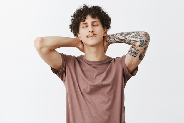 Guy feeling relieved stretching after sitting too long at work holding hands behind neck closing eyes lying back and enjoying evening being chill and calm having break over gray wall