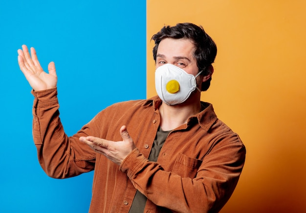 Guy in ffp2 face mask in a good mood on yellow and blue backgrounds
