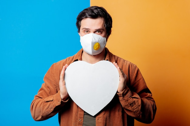 Guy in ffp2 face mask hold heart shape board on yellow and blue background