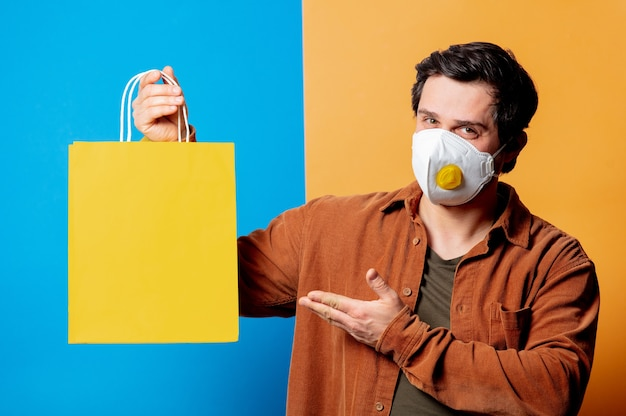 Guy in ffp2 face mask hold shopping bag on yellow and blue backgrounds