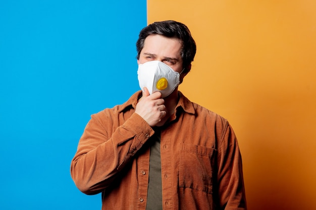 Guy in ffp2 face mask think abount something on yellow and blue background