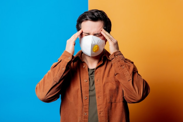 Guy in ffp2 face mask with headache on yellow and blue background