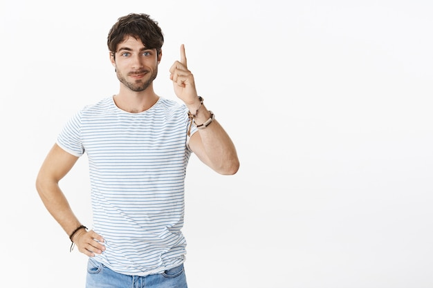 Guy finally mady decision raising index finger in eureka gesture with joyful smirk feeling ready order tasty food in cafe, holding hand on waist, pointing up posing over white wall