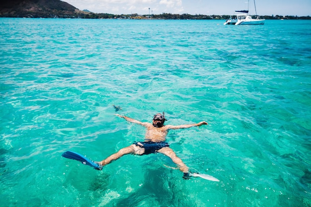 A guy in fins and a mask swims in a lagoon on the island of mauritius.