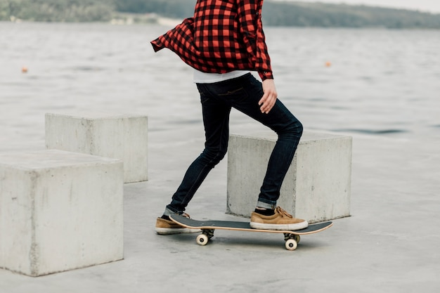 Guy in flannel skateboarding by the lake