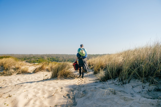A guy from behind walking through sandy dunes with lots of bags