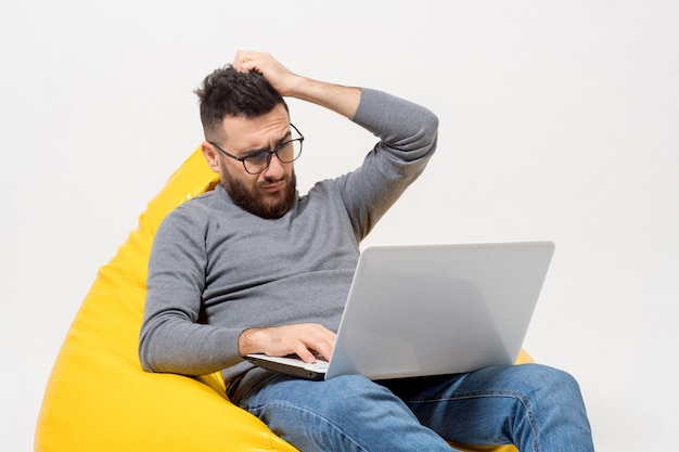 Guy frustrated while sitting on yellow pouf chair