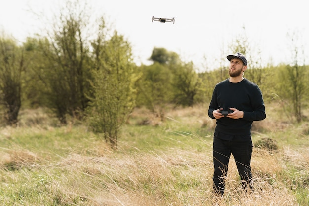 Guy in full black outfit with remote controller and flying a drone with field background