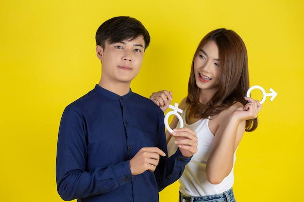 The guy and the girl are holding male and female symbol on yellow wall