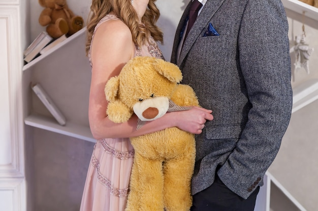 A guy and a girl are holding a toy of a plush bear. plush bear hold hands