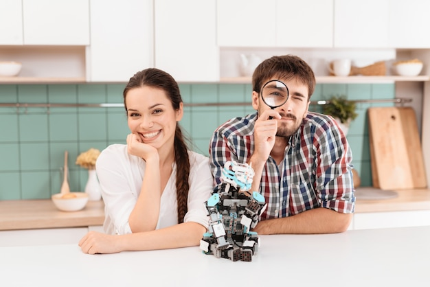 A guy and a girl are posing in the kitchen.