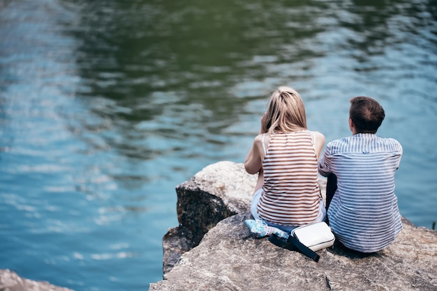 The guy and the girl are sitting on a cliff above the river and looking in front. rear view