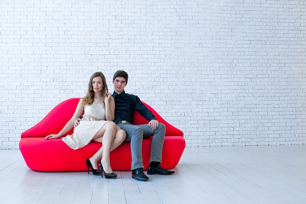 Guy and girl are sitting on sofa in form of red lips. beautiful couple in smart clothes holds hands.
