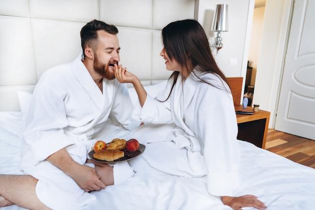 The guy and the girl bathrobe, girl feeds the guy fruit