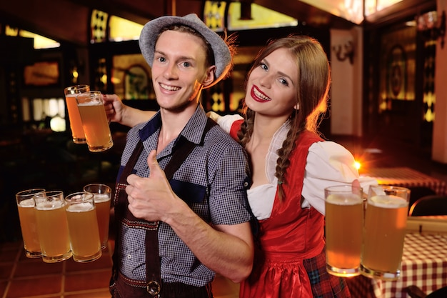 Guy and a girl in bavarian clothes holding a lot of mugs with beer on the pub background during the celebration of oktoberfest.