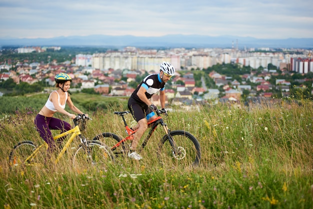Guy and girl on bicycles ride at hill among the grass with wildflowers