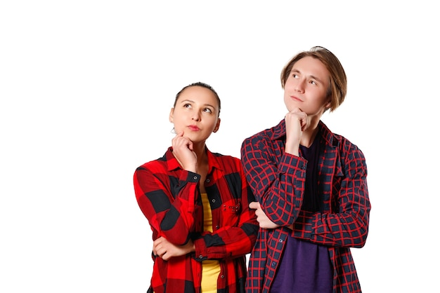 A guy and a girl in casual clothes, checkered shirts are standing and looking thoughtfully towards the copyspace. isolated on white background