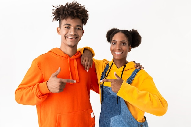 Guy and girl in colorful clothes pointing finger at each other, isolated over white wall