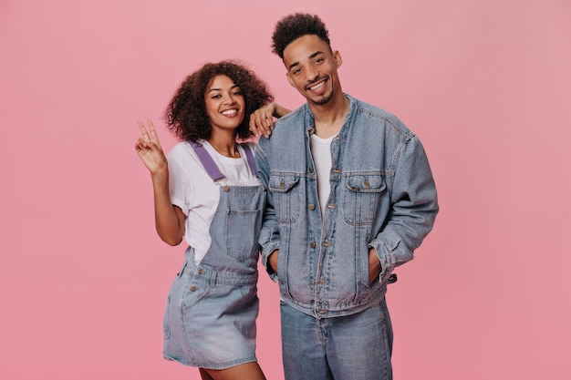 Guy and girl in denim outfits showing peace sign on pink wall