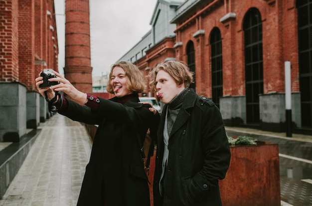 A guy and a girl doing a selfie on the camera and having fun