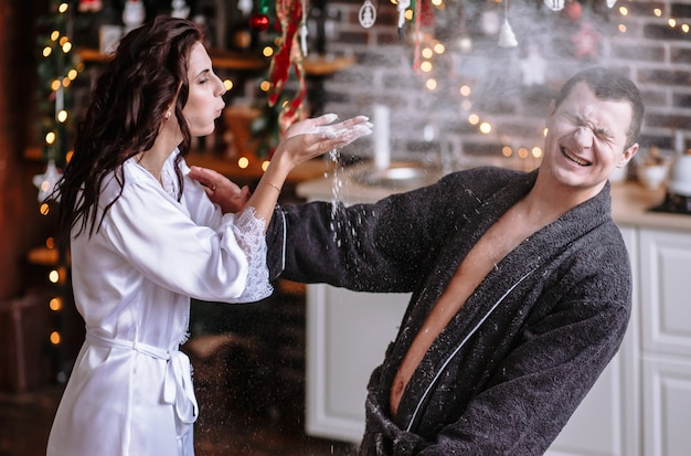A guy and a girl in dressing gowns in the kitchen, which is decorated for the celebration of christmas and new year. guys play with flour