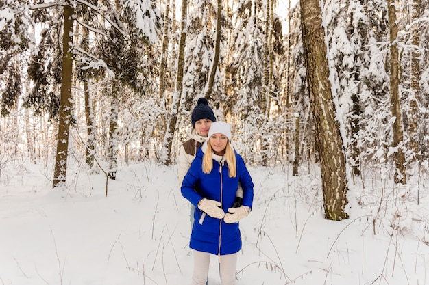 The guy and the girl have a rest in the winter woods.