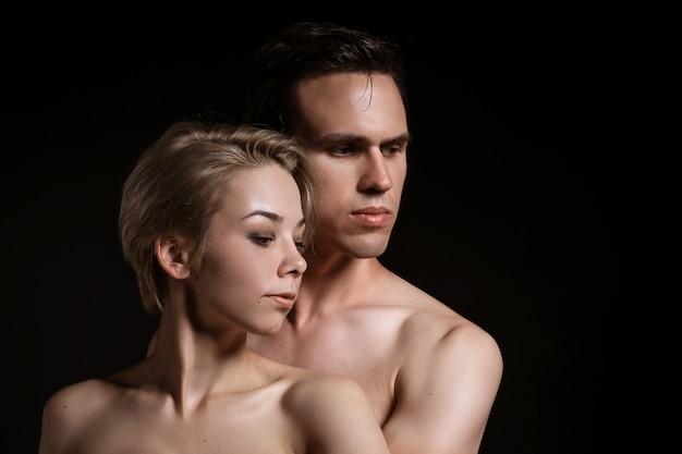 Guy and girl hugging, naked torso on black