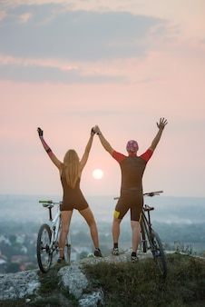 Guy and girl on mountain bikes keep the hands lifted upwards