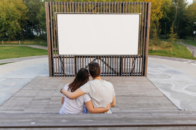 The guy and the girl in the park on the  of an open-air cinema