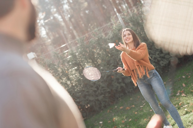 A guy and a girl play badminton during a picnic with friends.