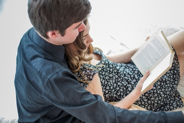 Guy and girl read a book lying on couch.