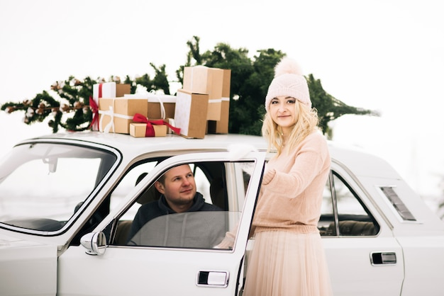A guy and a girl ride in a retro car decorated with a christmas tree and presents in a snowy forest. the concept of a winter christmas love story