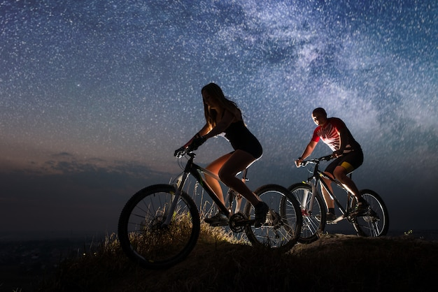 Guy and girl riding a bicycles on the hill at night