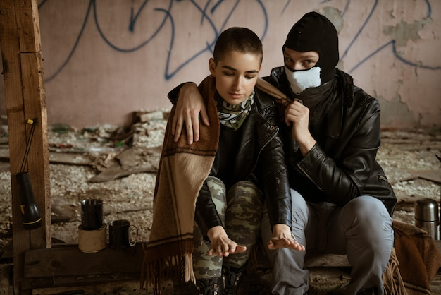 A guy and a girl in a slum sit together, the romance of the apocalypse