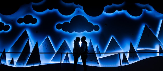 Guy and a girl stand face to face and hug on an abstract background with mountains and clouds.