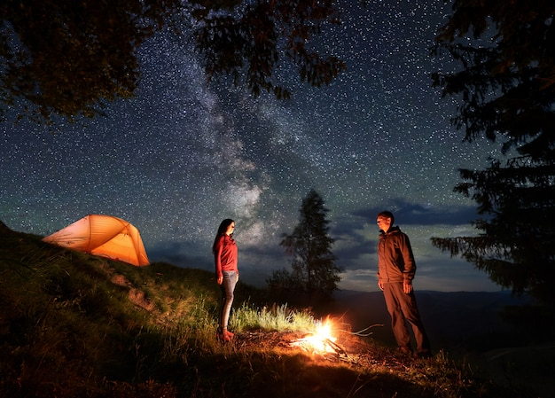 Guy and girl stand opposite each other and between them fire at night camping in mountains
