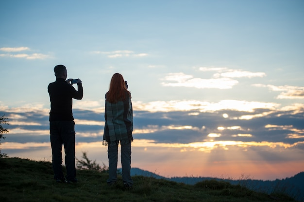 Guy and girl standing on the hill and photographed on phones sunrise. back view. morning in the mountains